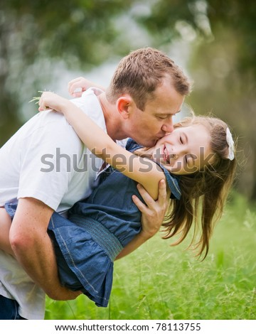 A 6 year old girl enjoying a moment of fun with her dad who is k