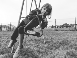 A 6-7 year old girl swinging on a swing against the background of a football field. Black and white monochrome image in retro or vintage style. Caucasian child