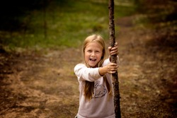 a 10-year-old girl with blonde hair climbed a tree in the forest, selective focus