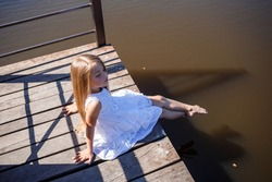 A 7-year-old girl with long blond hair by the lake sits on a clutch with legs in the water. She splashes her feet in the lake. Barefoot girl in a white dress with long hair.