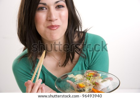A 29 year old woman takes a bite of a Sushi Roll
