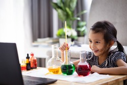 A 5 years old asian little girl  measuring the temperature of hot and cold water for easy science experimental online class, new normal and distance learning, e-learning for kid in covid-19 pandemic.
