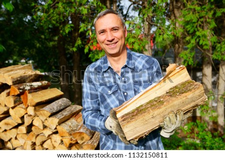 A 50 years old caucasian man wearing a bleu shirt is smiling at us while piling his wood for the winter season, in order to heat the house.