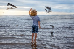 A 4 years old kid (boy) with curly hair in a sailor's striped vest feeds gulls on the beach. He jumps like he's dancing and standing on tiptoe like ballet dancer. Back view. Cloudy weather, sunset.