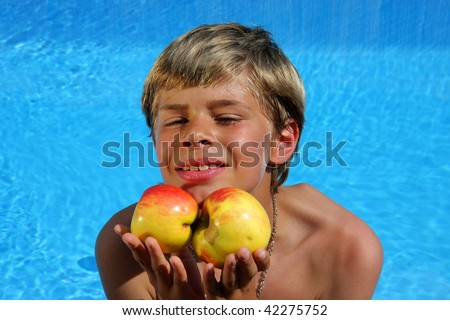 a 10-years old smiling American - German boy sitting at a swimming pool and presenting delicious apples in the summer sun