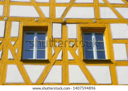 A yellow and white framework house