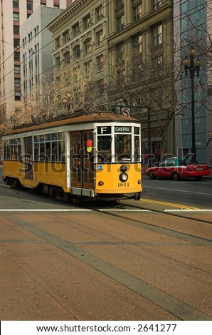 A yellow and white 1928 Peter Witt trolley car from Milan, Italy, in downtown San Francisco