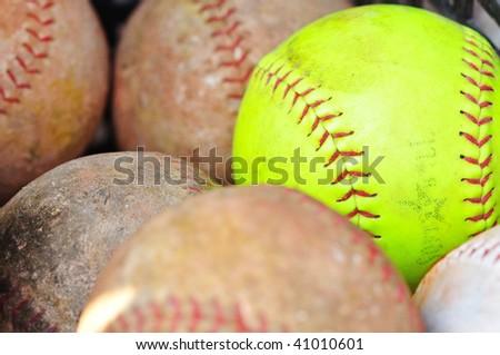 a yellow baseball and brown baseballs