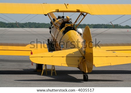 A yellow biplane sitting ready for take-off.