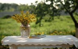 A yellow bouquet in a transparent vase and a green notebook on the table . Still life outdoors on the street. Yellow flowers in a vase in the sun