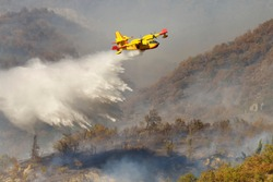 A yellow Canadair or water-bomber in action on a wildfire