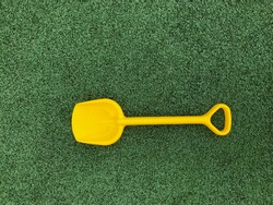 A yellow child's shoulder blade lies on a green artificial turf.