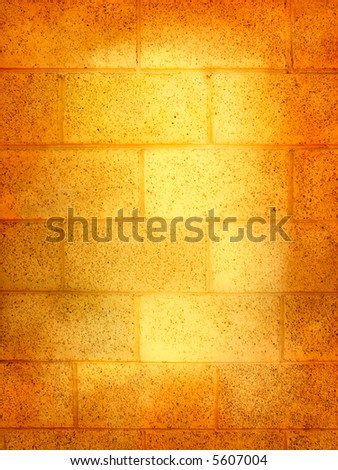 A yellow cinder block wall with vignette and highlights.