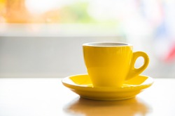 A yellow coffee cup was placed on a wooden table, the background blur in the coffee shop. It's a relaxing time And breaks from work Use a close-up photography perspective.