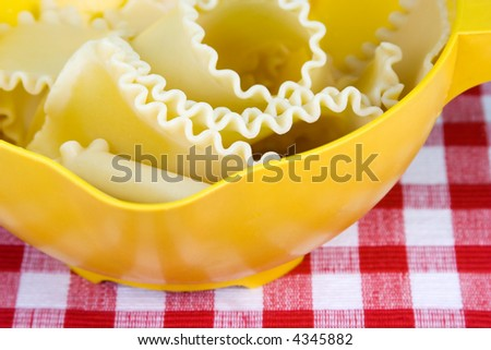 A yellow colander full of cooked lasagna noodles. INSPECTOR: Please note the plastic colander is textured and that texture shows towards the bottom in the reflection. It is not noise. Thanks!