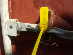 A yellow colored container seal is in locked position on a red colored rusted container lock.