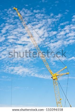 A yellow crane against a bright blue sky