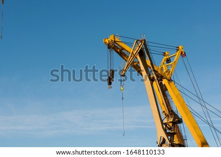 A yellow crane under the sunlight and a blue sky in Portugalete in Spain