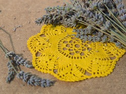 A yellow crochet cotton doily with dried lavender on a textured wooden fibre background.