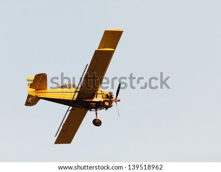 A yellow crop duster from below