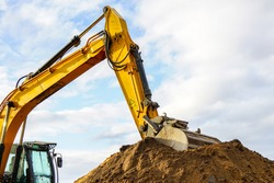 a yellow excavator boom with a bucket digs a pile of earth