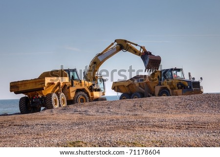 A yellow excavator digging on beech with a truck carry the sand - stock photo