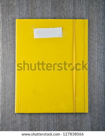 A yellow folder with empty white paper label