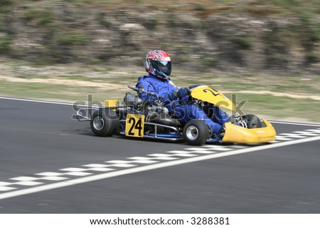 A yellow gearbox go kart crossing the finish line