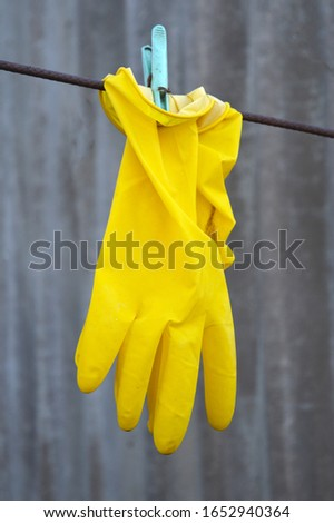 A yellow glove hangs on a clothespin.