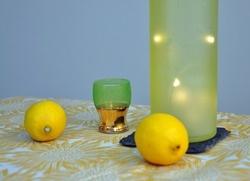 A yellow green bottle with shiney twinkling lights, drinking glass and two fresh lemons on table with a blue grey background and a light orange tablecloth. Studio shot still life