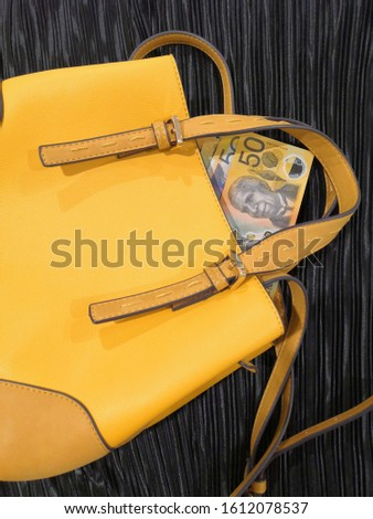 A yellow handbag on the black background