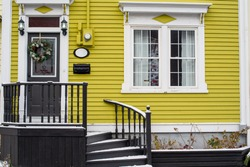 A yellow house with white windows, black door, letterbox and wreath. The entrance has two light fixtures, number plate and curved steps. There's a light layer of snow on the landing.