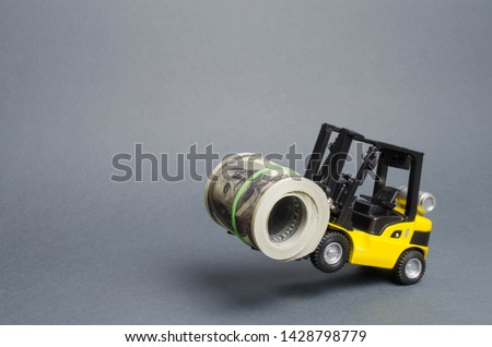 A yellow loader stands on the rear wheels holding a big bundle of dollars. concept of attracting investment, issuing concessional loans for business development. High profitability of stocks and bonds #1428798779