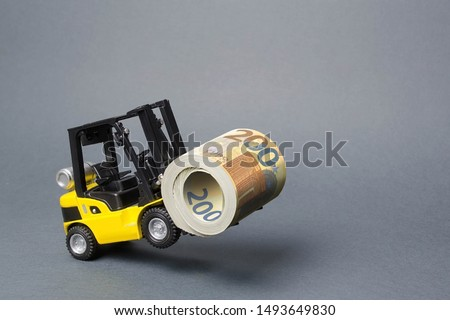 A yellow loader stands on the rear wheels holding a big roll bundle of Euro. concept of attracting investment, issuing concessional loans for business development. High profitability of stock bonds #1493649830