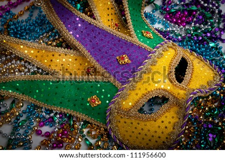 A yellow Mardi Gras jester mask and beads