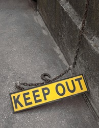 A yellow metal fluorescent keep out sign on a rusty metal chain on a concrete floor next to a wall