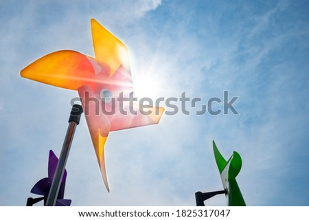 Photo of  A yellow pinwheel that rotates in a clear sunlit sky.