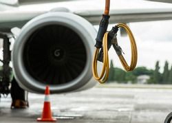 A yellow power cable hangs in front of an airplane engine. Selected focus on the yellow power cable