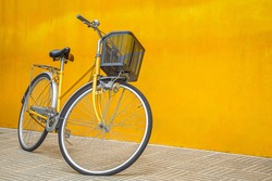 A yellow retro bicycle parking against yellow wall. Vintage woman bike with basket in front.