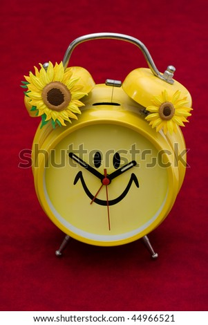 A yellow retro smiley face clock on a red background, smiley clock