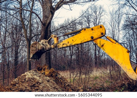 A yellow rusty industrial excavator with a bucket lying on the ground, digging the ground at a construction site in a pond forest.