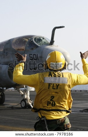 "A ""Yellow Shirt"" Aircraft Director Loads an EA-6B Prowler onto a Catapult on a Nuclear Aircraft Carrier"