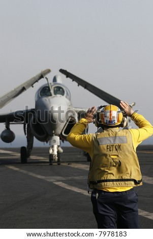 "A ""Yellow Shirt"" Aircraft Director Taxis an EA-6B Prowler Aboard a Nuclear Aircraft Carrier"