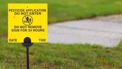 A yellow sign place on a residential lawn reads Pesticide applicatiion, do not enter for 24 hours.