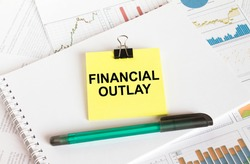 A yellow sticker with text Financial Outlay is in a Notepad with a green pen financial charts and documents. Business and financial concept