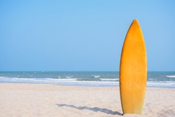 A yellow surf board was stabbed down into the white sand tropical beach on the sunny day with wave and sea background, copy space, sport and recreation concept, holiday and vacation concept