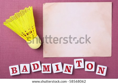 A yellow synthetic badminton shuttlecock next to a piece of paper. Add your text to the paper.
