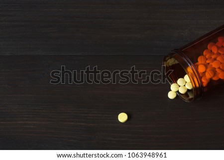 A yellow tablet medication on wooden background and a plastic container of drug with many tablets of medications inside #1063948961