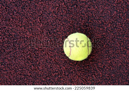 A yellow tennis ball on the ground