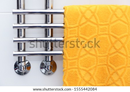 A yellow towel is dried on a heated towel rail.Heated Towel Rack. Polished Stainless Steel.Hotel Fabric. Wall style. Towel warmer for the bathroom.